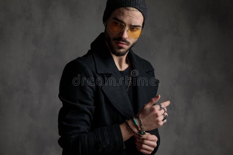 Hombre interesante que arregla sus pulseras foto de archivo libre de regalías
