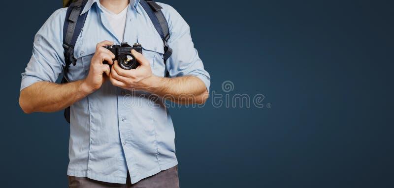 Hombre irreconocible del Blogger del viajero del hombre con la cámara de la mochila y de la película en fondo azul Caminar concep fotografía de archivo libre de regalías