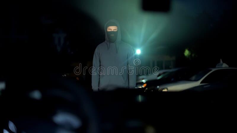 Hombre irreconocible en la situación de la máscara delante del coche, conductor que amenaza, crimen foto de archivo
