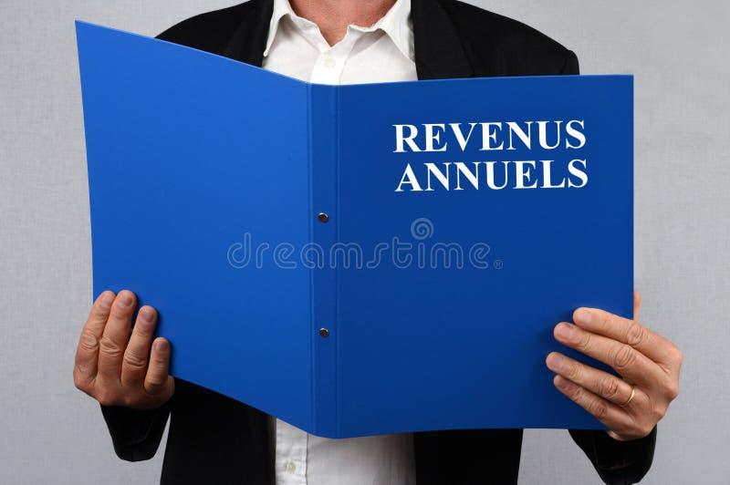 Hombre irreconocible que lee el fichero de los ingresos anuales escrito en francés fotos de archivo libres de regalías