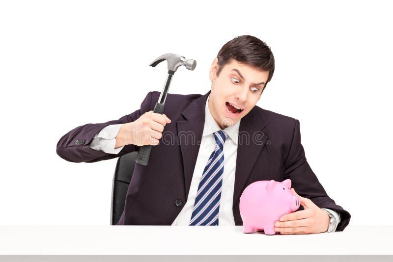 Hombre irritado que intenta romper una hucha con un martillo foto de archivo