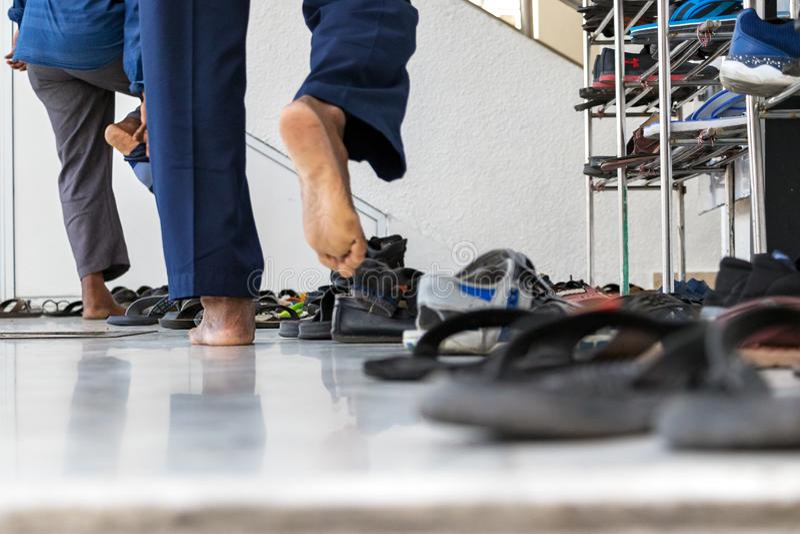 Hombre islámico que saca sus zapatos antes de entrar a una mezquita en varón, Maldivas foto de archivo