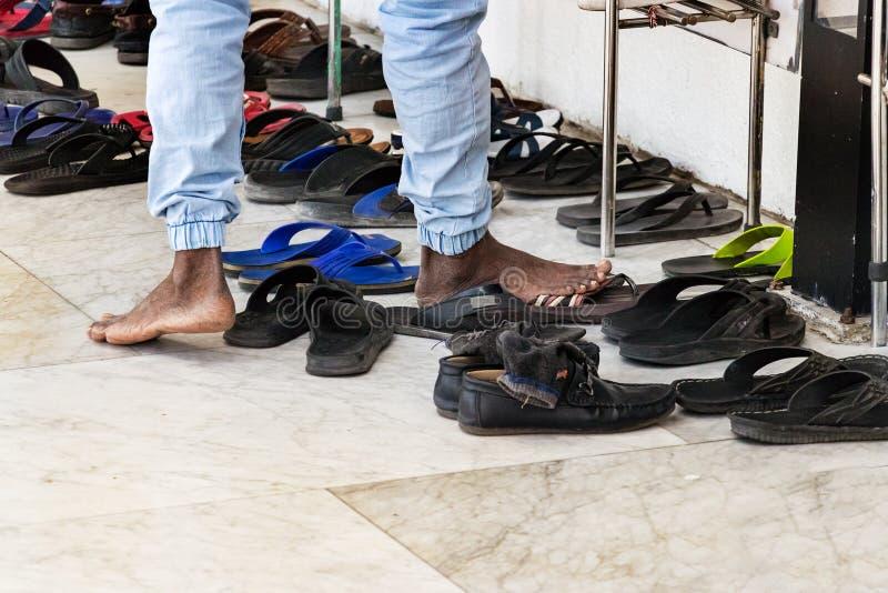 Hombre islámico que saca sus zapatos antes de entrar a una mezquita en varón, Maldivas fotografía de archivo