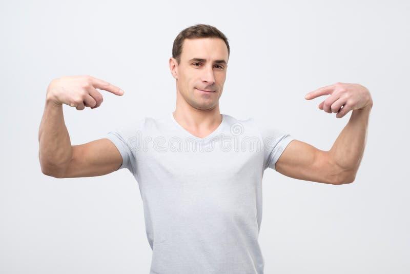 Hombre italiano en la camiseta blanca, colocándose, señalándose y mirando con la cara seria del egoísta imagen de archivo libre de regalías