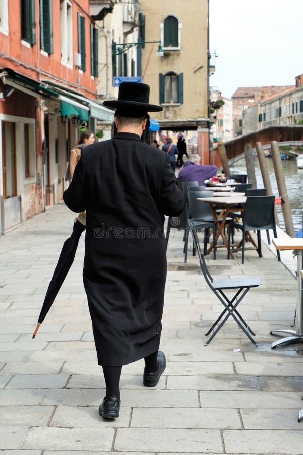 Hombre jasídico judío con un paraguas que camina en la calle en el cuarto judío imágenes de archivo libres de regalías