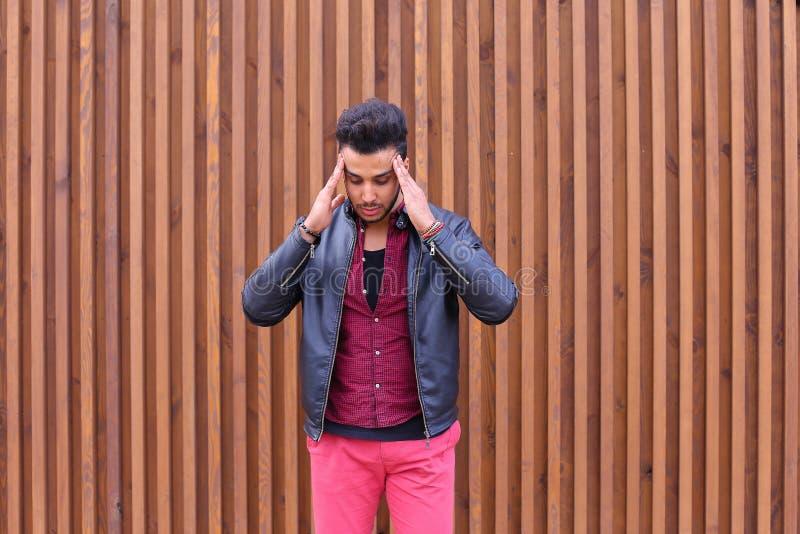 Hombre joven árabe atractivo, estudiante Feels Headache, con la cabeza a foto de archivo libre de regalías