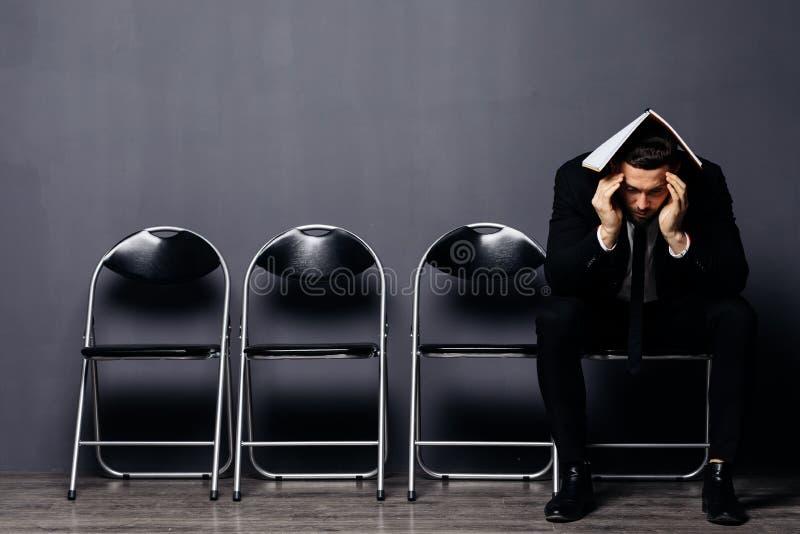 Hombre joven aburrido en el traje formal que se sienta en silla de la oficina en sala de espera con el documento o el curriculum  fotografía de archivo