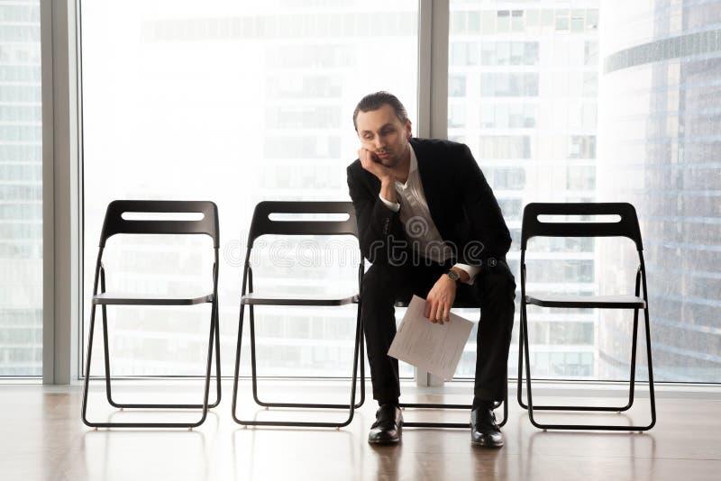 Hombre joven aburrido en el traje que se sienta en sala de espera imágenes de archivo libres de regalías