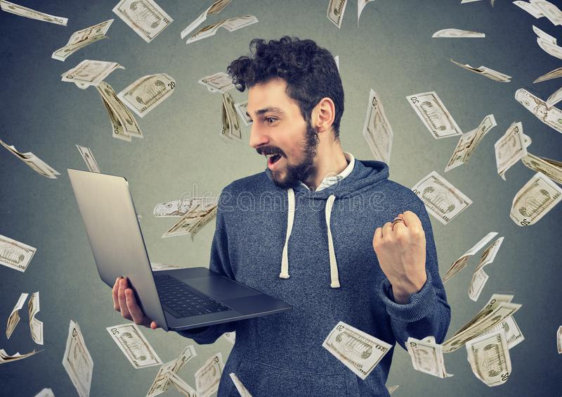 Hombre joven acertado que usa el ordenador portátil que construye el dinero en línea de la ganancia de negocio fotos de archivo libres de regalías