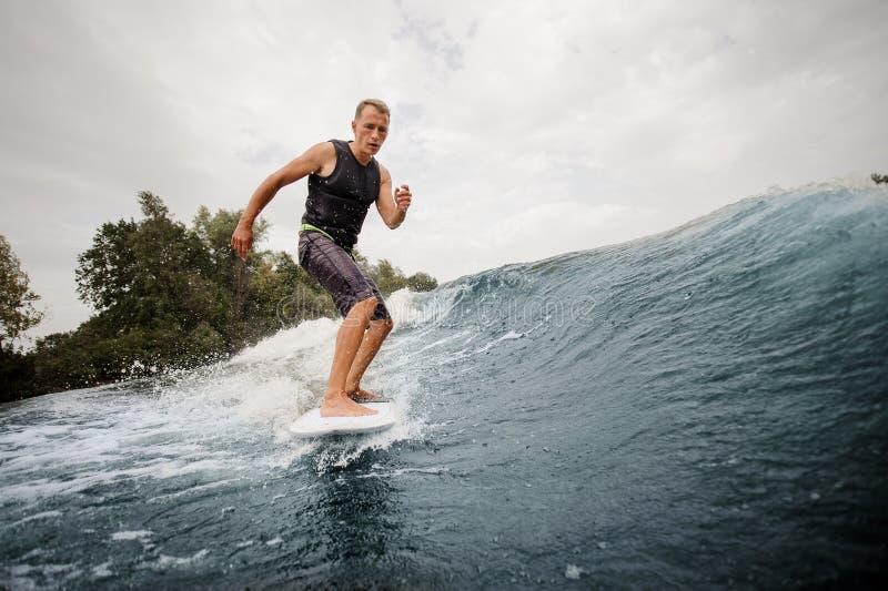 Hombre joven activo wakesurfing en el tablero abajo del alto wav azul imagen de archivo libre de regalías
