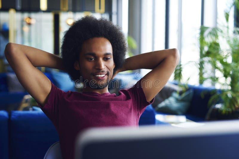 Hombre joven, afroamericano que se relaja en la oficina imagen de archivo libre de regalías