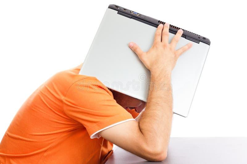 Hombre joven agotado que cubre su cabeza con su ordenador portátil foto de archivo