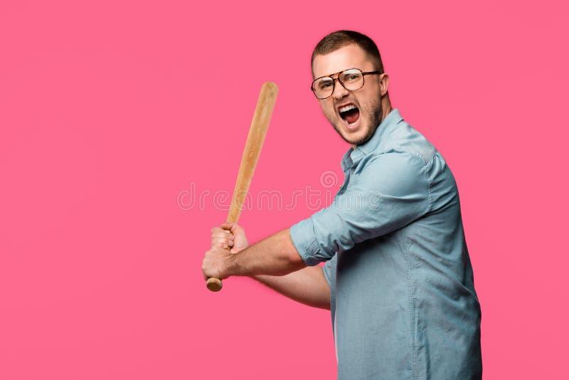 hombre joven agresivo en las lentes que sostienen el bate de béisbol y que gritan en la cámara aislada imagenes de archivo