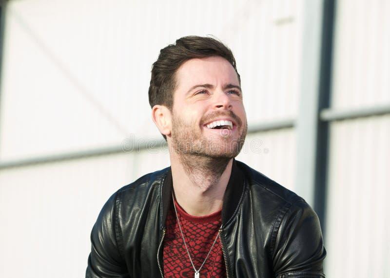 Hombre joven alegre con la barba que ríe afuera imagen de archivo libre de regalías