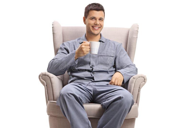 Hombre joven alegre con una taza que se sienta en una butaca fotografía de archivo libre de regalías