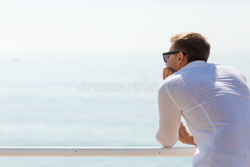 Hombre joven alegre en la camisa blanca que presenta en la cámara al aire libre imagen de archivo
