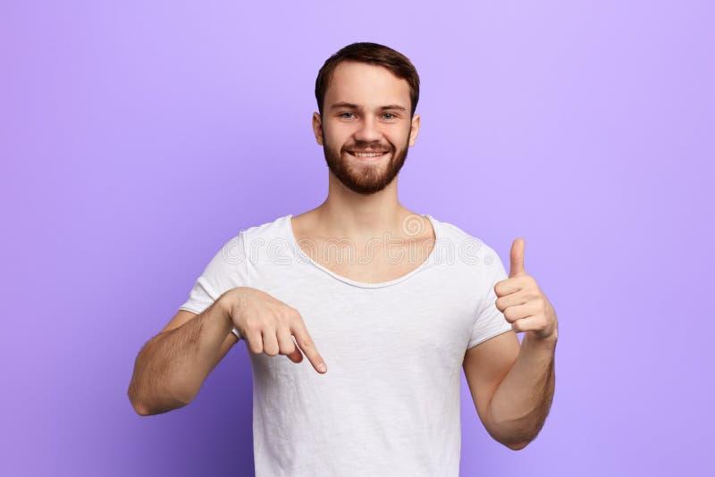 Hombre joven alegre en la camiseta blanca que señala abajo y que muestra el pulgar para arriba imagen de archivo
