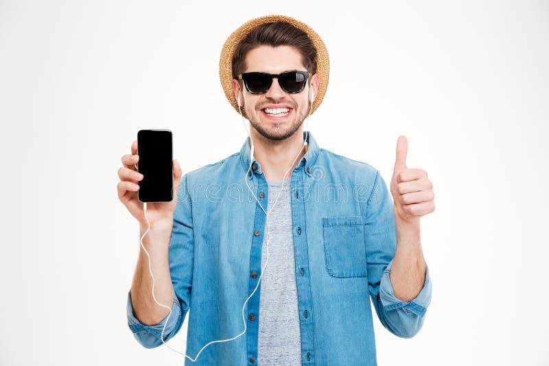Hombre joven alegre en los auriculares que muestran el teléfono celular de la pantalla en blanco fotografía de archivo libre de regalías