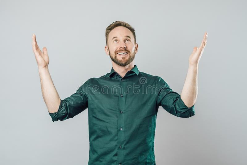 Hombre joven alegre que aumenta los brazos y que mira para arriba foto de archivo libre de regalías