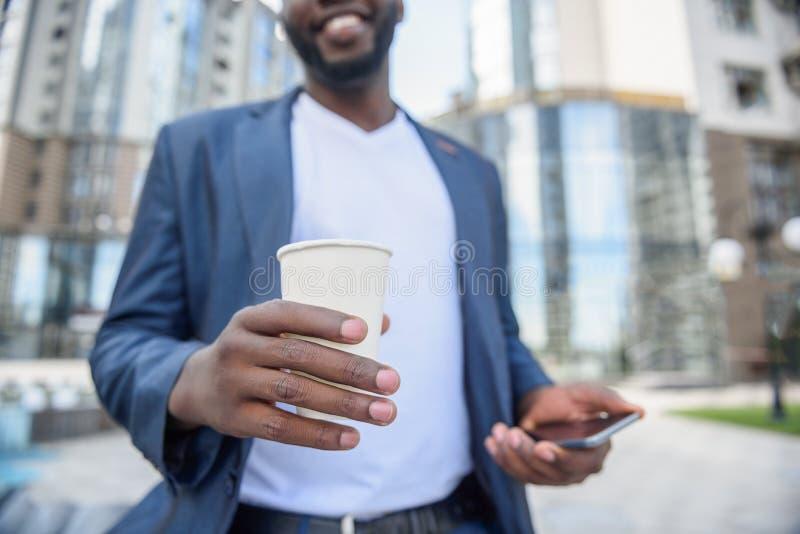 Hombre joven alegre que disfruta de la bebida caliente al aire libre fotografía de archivo