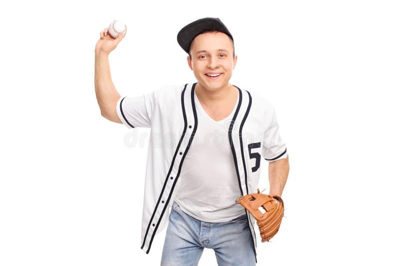 Hombre joven alegre que lanza un béisbol fotos de archivo