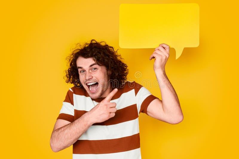 Hombre joven alegre que se?ala en el globo de discurso fotos de archivo