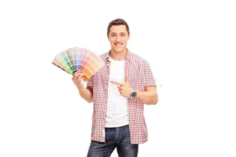 Hombre joven alegre que sostiene una muestra del color imagenes de archivo