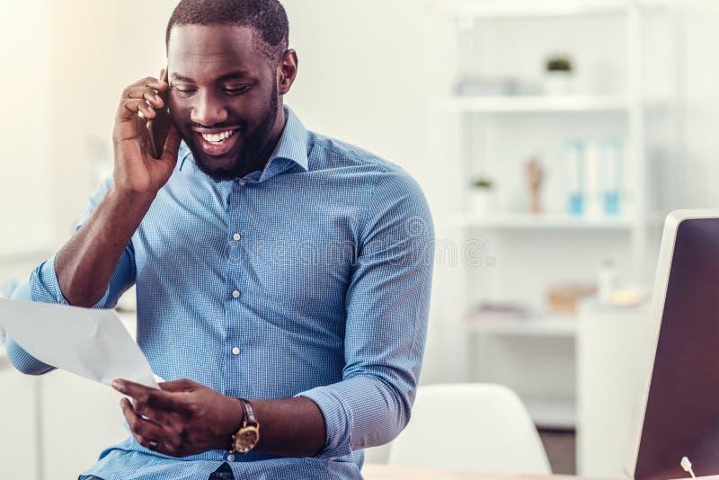 Hombre joven alegre que tiene conversación telefónica fotografía de archivo