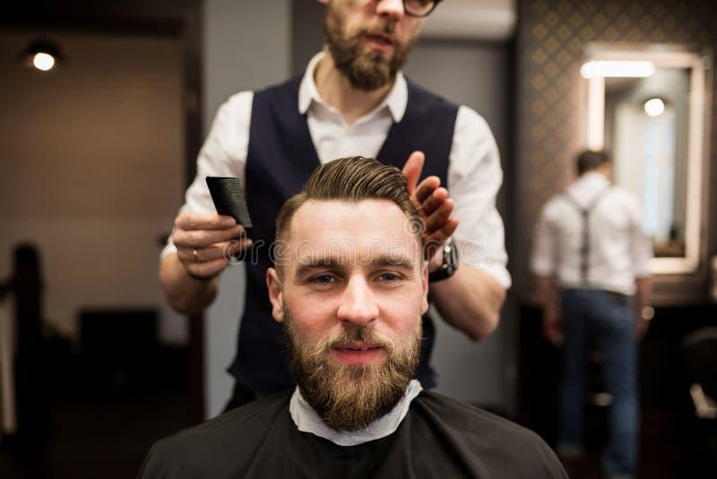 Hombre joven alegre que tiene pelo cortado en el salón del peluquero imagenes de archivo