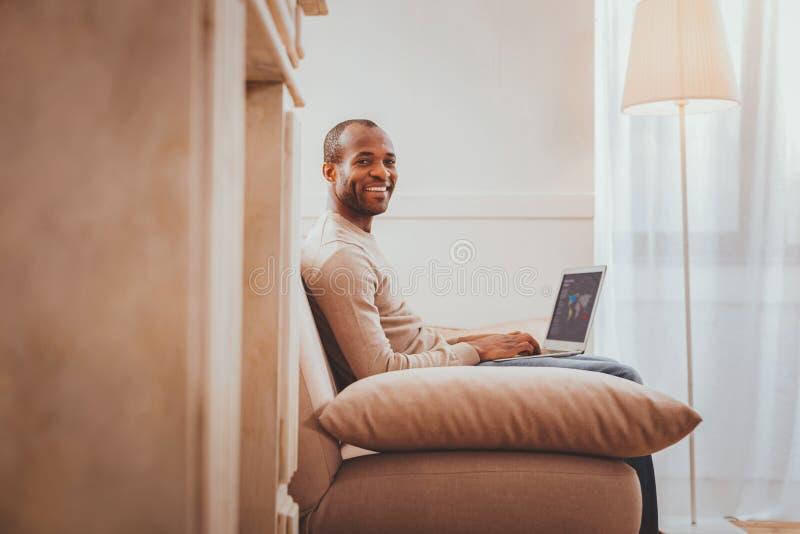 Hombre joven alegre que trabaja de hogar imagen de archivo