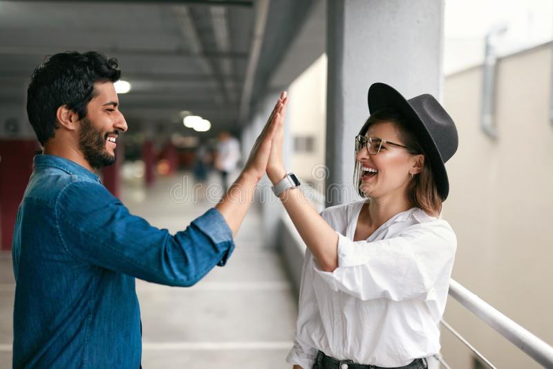 Hombre joven alegre y mujer que dan altos cinco el uno al otro imagen de archivo libre de regalías