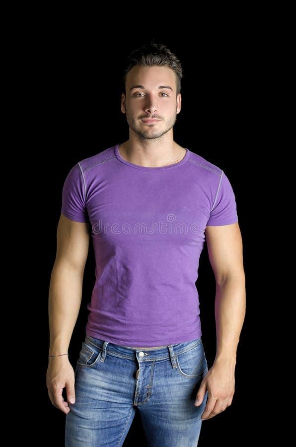 Hombre joven amistoso hermoso que se coloca en camiseta y vaqueros imagen de archivo libre de regalías