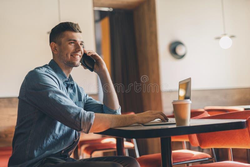 Hombre joven amistoso que disfruta de charla del teléfono en el café y la sonrisa imagen de archivo libre de regalías