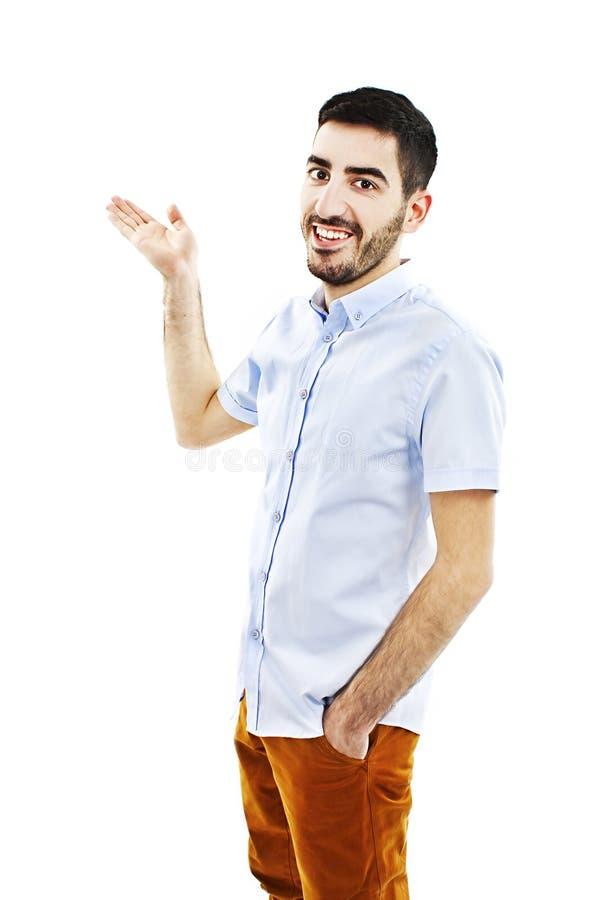 Hombre joven amistoso que señala a su lado y que mira en la cámara foto de archivo