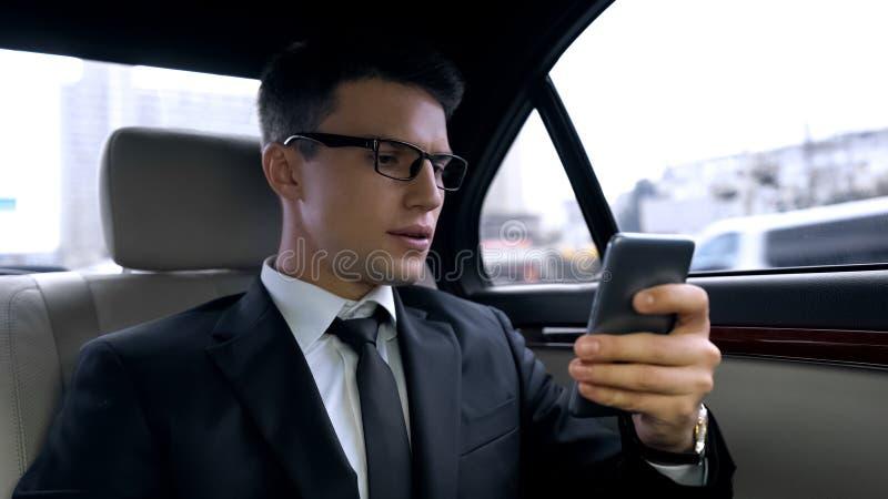 Hombre joven ansioso en el traje que recibe el mensaje con las malas noticias, paseo en auto de lujo imagenes de archivo