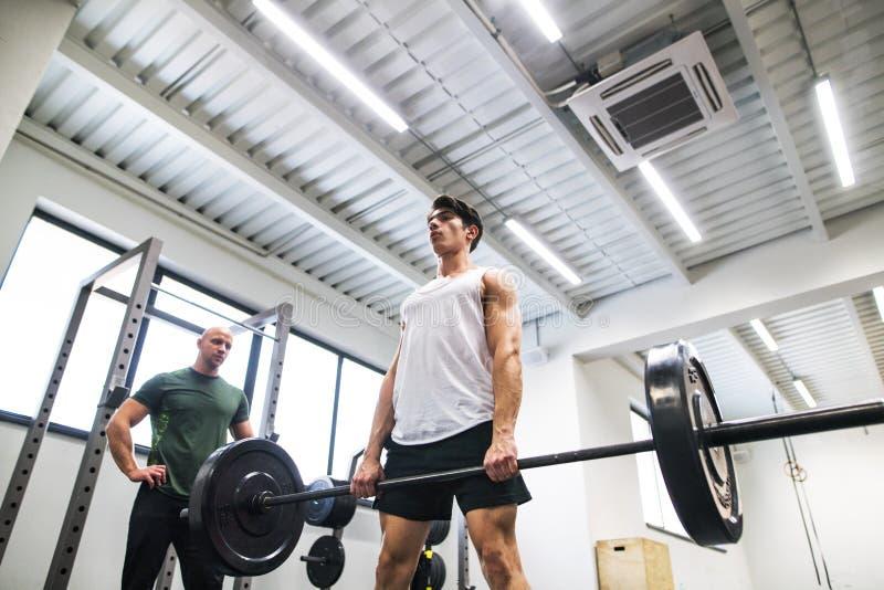 Hombre joven apto con un instructor personal en gimnasio que se resuelve, barbell de elevación imágenes de archivo libres de regalías