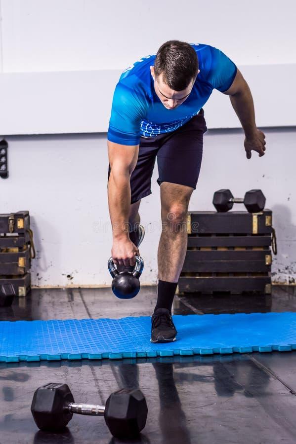 Hombre joven apto que hace ejercicio de la campana de la caldera en el gimnasio fotografía de archivo