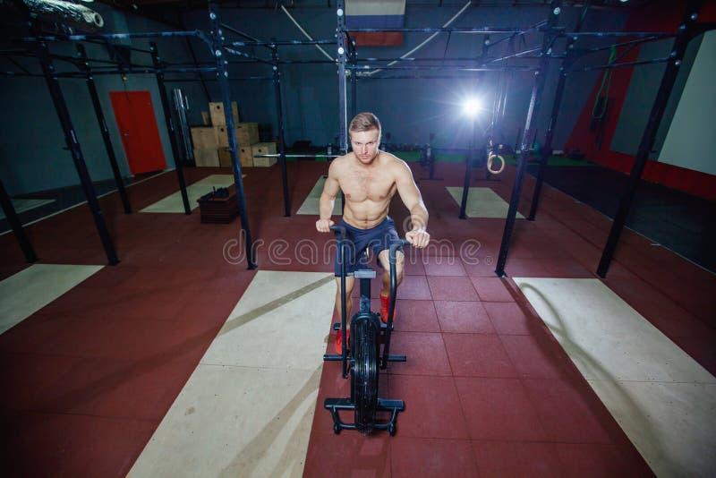 Hombre joven apto que usa la bicicleta estática en el gimnasio Varón de la aptitud usando la bici del aire para el entrenamiento  fotografía de archivo libre de regalías