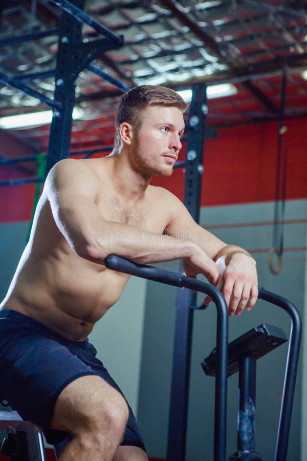 Hombre joven apto que usa la bicicleta estática en el gimnasio Varón de la aptitud usando la bici del aire para el entrenamiento  fotos de archivo