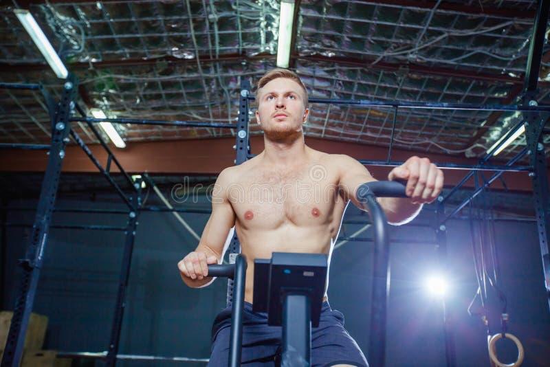 Hombre joven apto que usa la bicicleta estática en el gimnasio Varón de la aptitud usando la bici del aire para el entrenamiento  fotografía de archivo