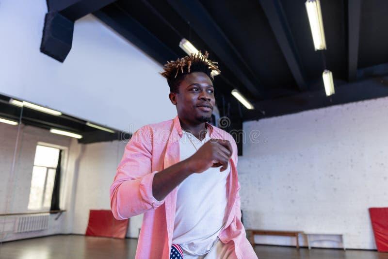 Hombre joven apuesto alegre con los dreadlocks cortos que llevan la camisa rosada fotografía de archivo libre de regalías