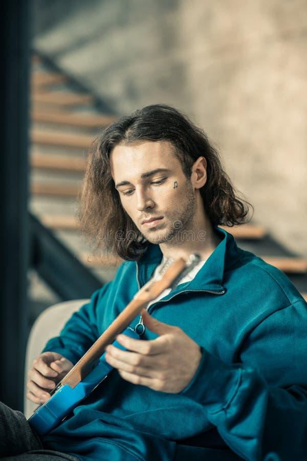 Hombre joven apuesto descuidado que entona secuencias en su guitarra foto de archivo
