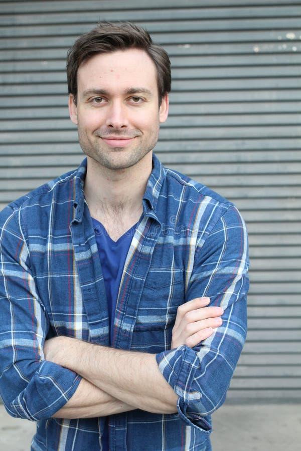 Hombre joven apuesto natural que sonríe con los brazos cruzados foto de archivo