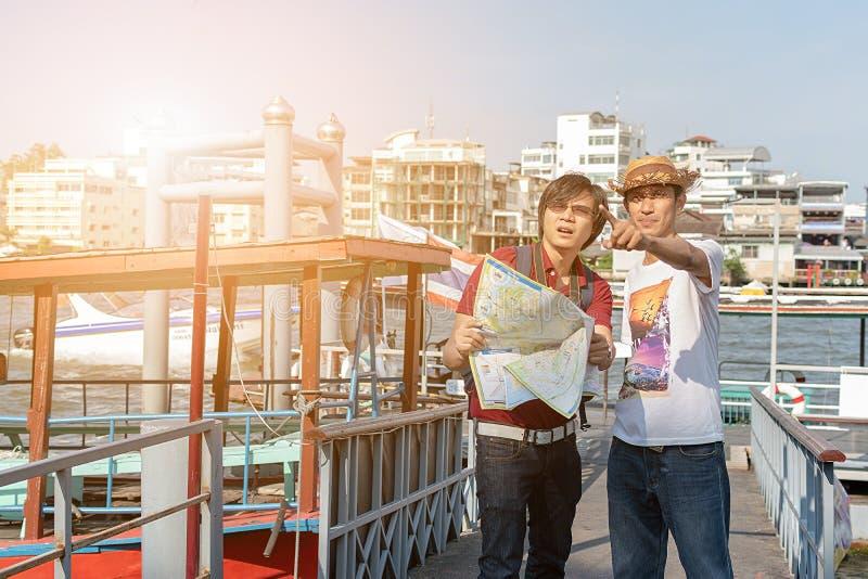 Hombre joven asiático de la mochila como turista que mira el travell del mapa fotografía de archivo