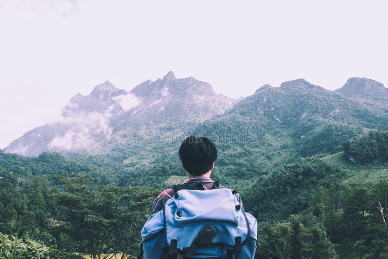 Hombre joven asiático en camisa escocesa y el sombrero negro que caminan en el pico de montaña sobre las nubes y el caminante de  foto de archivo libre de regalías