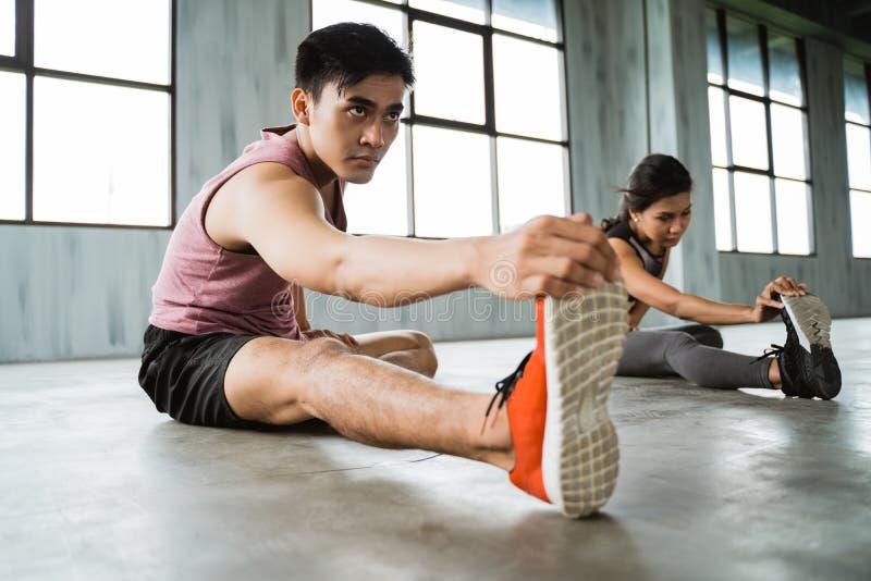 Hombre joven asiático que hace las piernas que estiran antes de ejercicio de la base imagenes de archivo