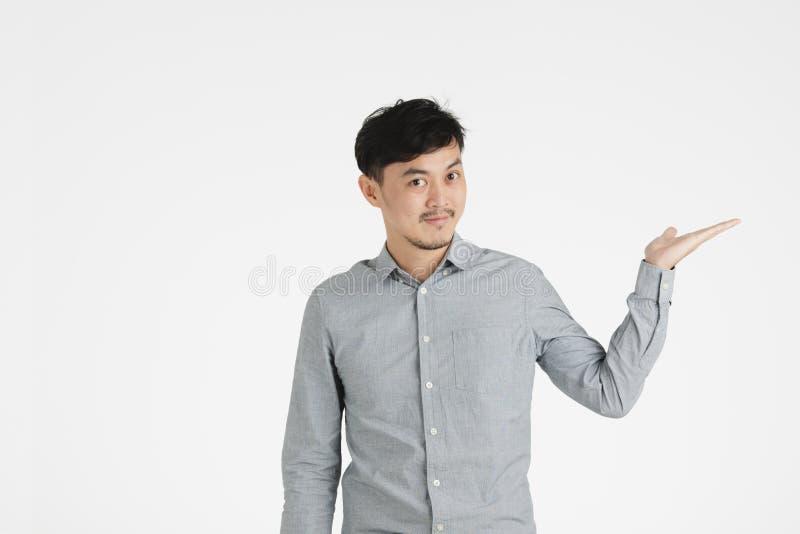 Hombre joven asiático que lleva a cabo algo imaginario fotos de archivo