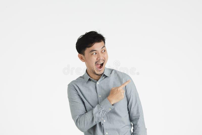 Hombre joven asiático que señala en algo imaginario fotos de archivo libres de regalías