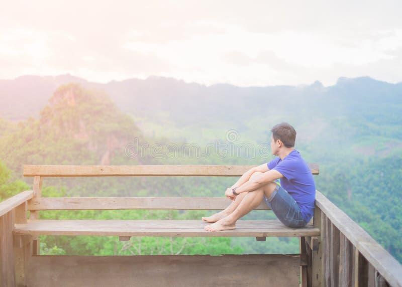 Hombre joven asiático, sentándose en delante del balcón él está pensando algo fotos de archivo