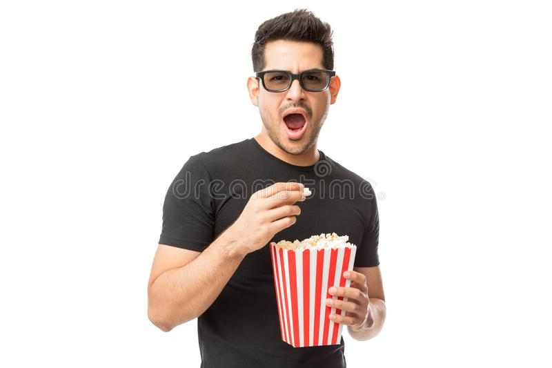Hombre joven asustado que lleva los vidrios 3D mientras que comiendo palomitas imagen de archivo